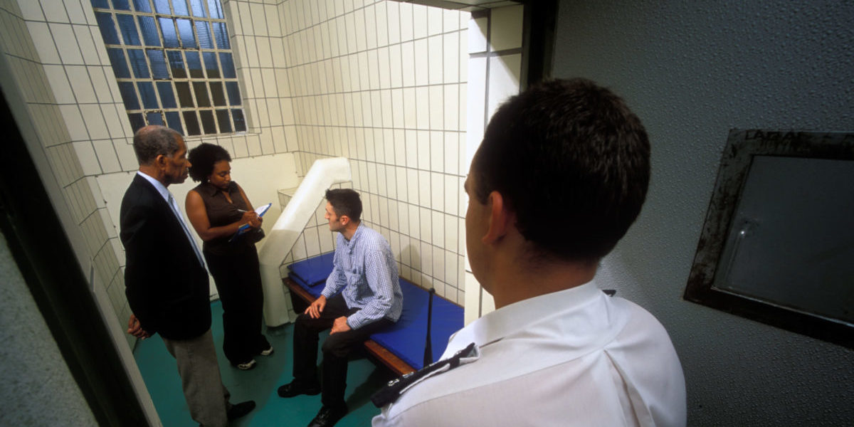 Two independent custody visitors in a police cell talked to a detained person, while a custody officer stands outside the open door