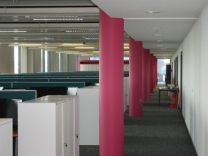 Open plan office space with pink columns along the walkway