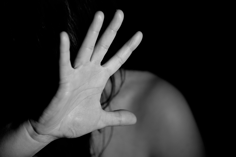 Domestic abuse; black and white photo of a hand held up