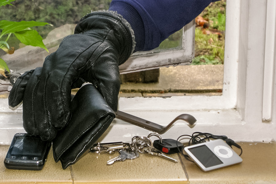Home crime prevention: a gloved hand reaching in through a window picking up a wallet