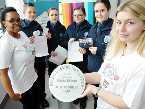 Youth Commission members and police cadets holding the cover of the time capsule