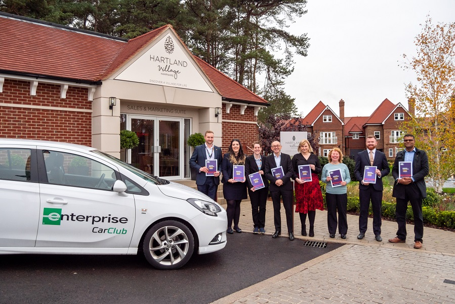 Group of 8 people stood in a line holding business hate crime guides, next to an Enterprise rental car. Group includes deputy PCC Enzo Riglia, and representatives of the Safer North Hampshire Partnership and Enterprise Rent-A-Car