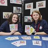 Two Youth Commission members hold postcards, with more on a bue tablecloth in front of them; pictures are displayed on a black board behind them.