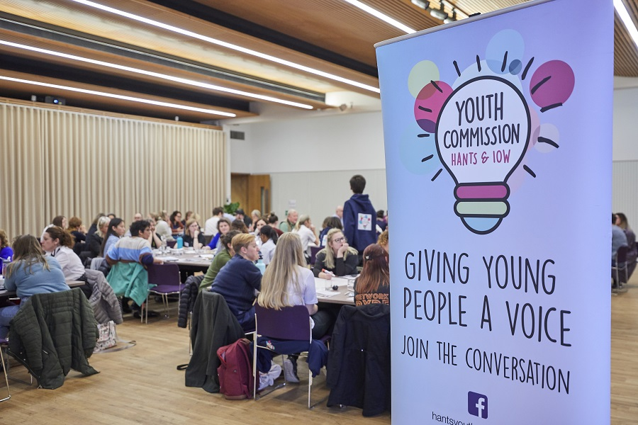 "Lots of people seated in a hall, with a banner for the Youth Commission in the foreground which has their logo and says ""giving young people a voice"" and ""join the conversation"""