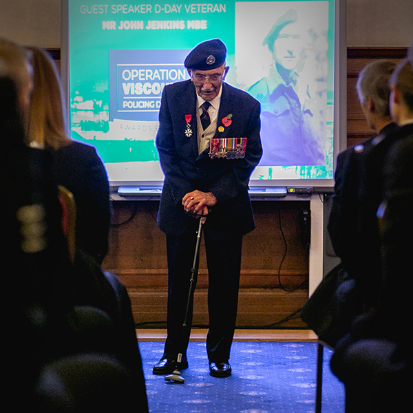 John Jenkins in 2019 at the Op Viscount event; John is stood, leaning on a stick and is wearing his medals and beret.