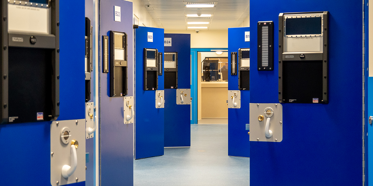 A view through the Eastern PIC custody block past open cell doors with the custody desk in the background.