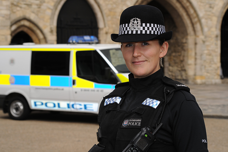 A police officer is stood in the foreground in uniform, with a police van and the Southampton Bargate behind her.