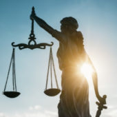 A photo of the statue of justice who is blindfolded while holding scales and a sword. The sun flares under the right arm of the statue.