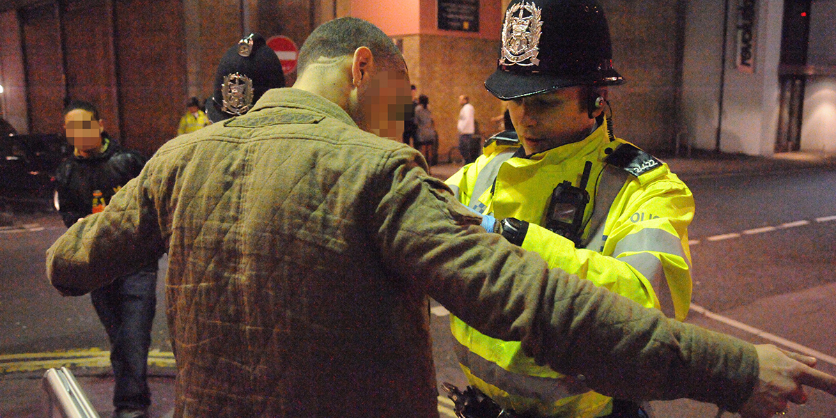 A police officer is searching a man in a khaki jacket on a street at night. The man's face is blurred out.