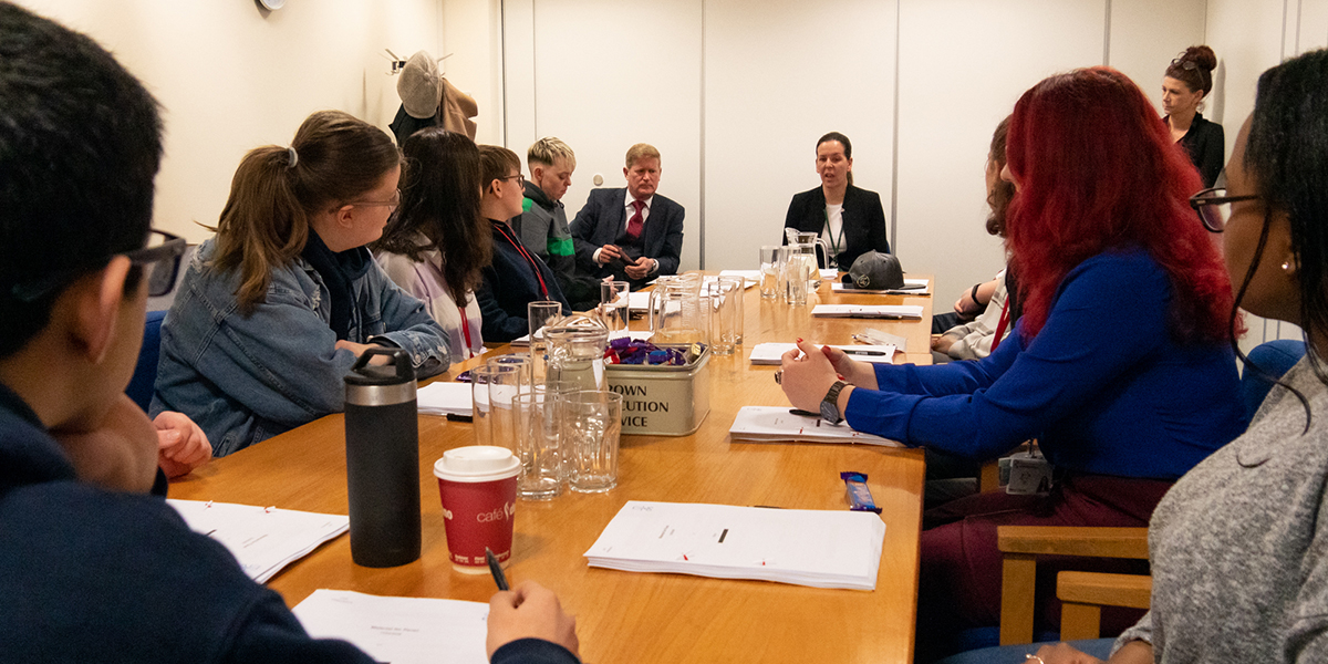 Youth Commission members sit around a conference table, with chief prosecutor Jo Jakymec at the head of the table