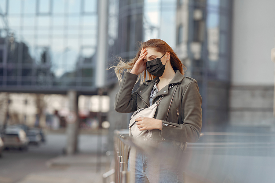 Woman in an empty urban setting ,wearing a face covering